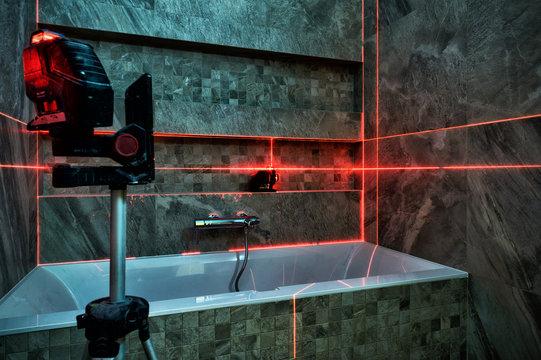 Red laser light lines for level measure during bathroom renovation