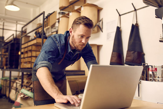 Serious young business owner using laptop in his workshop