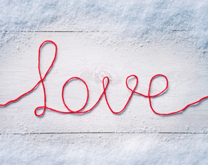 "Valentines background  with snow. Word ""love"" on white wooden background. Valentines Day background"