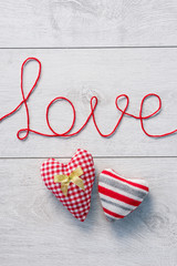 "Valentine's hearts and ""love"" on white wooden background. Valentines Day concept"