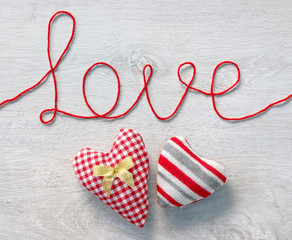 "Word ""love"" and two hearts on white wooden background. View from above. Valentines Day concept"