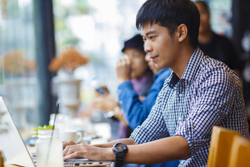 Smiling asian businessman using laptop in coffee shop