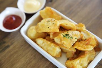 fried potatoes on wood background