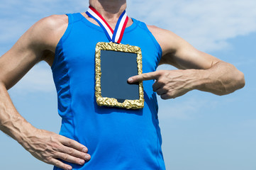 Athlete using tablet hanging as gold medal on red, white, and blue ribbon against blue sky