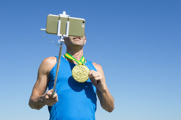 Gold medal athlete smiling for a selfie with a mobile phone on a selfie stick
