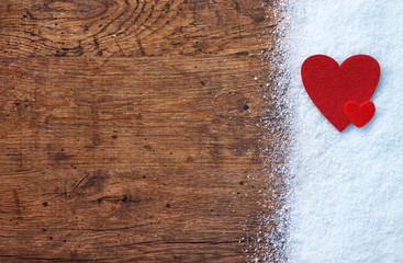 Big and small red hearts on snow on the wooden table. View from above. Valentines Day concept