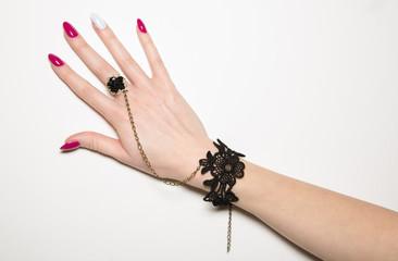 Manicure: mano da donna con bracciale e anello nero