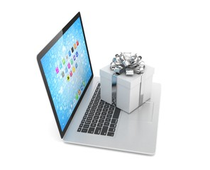 Gift box with ribbon bow on laptop keyboard