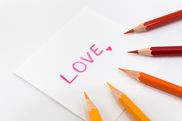"wording  ""Love"" with little heart on the small paper , encircle with color pencils"