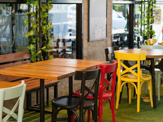 Wooden dining tables and multi color chairs in restaurant.