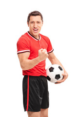 Happy football player holding a ball