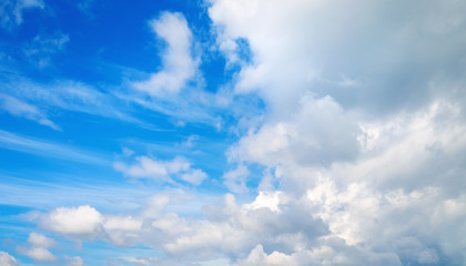Sky background with white cumulus clouds on a sunny day. Panoramic shot.