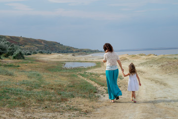young mother with a child walking along the seashore