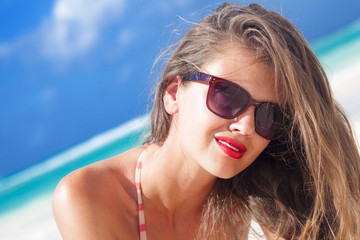 young woman with red lips and in stripy swimsuit at tropical beach