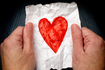 Young man holding crumpled piece of paper with red heart