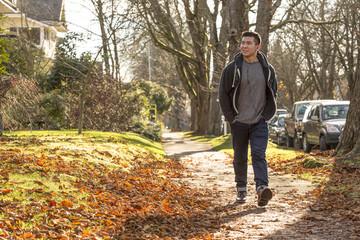 Mixed race man walking on suburban street