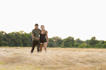 Couple walking together in rural field