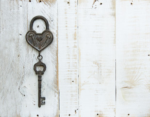 Heart and key on white wooden background