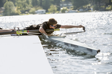 Teenage boy preparing scull from dock over lake