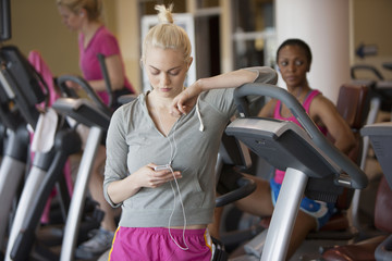 Caucasian woman using mp3 player in gym