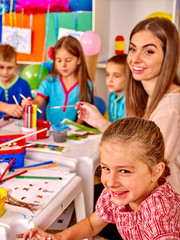 Large group of kids with female teacher painting on paper at table in kindergarten .