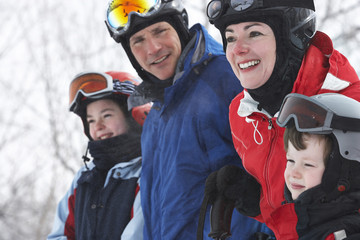 Caucasian family wearing ski gear in snow