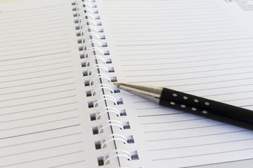 primo piano di biro e agenda calendario su scrivania d'ufficio