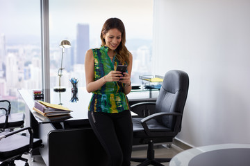 Young Latina Businesswoman With Phone In Modern Office