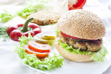 Homemade hamburger, vegetables and herbs. Homemade hamburger, sliced tomatoes, onion, pepper, lettuce and dill on wooden board.