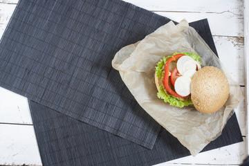 Homemade hamburger on papper, black makisu on white wooden table.
