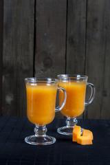 Fresh pumpkin juice in tall glass, pieces of fresh pumpkin on the black desk