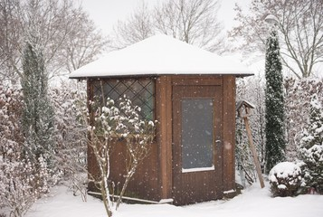 Picture of the garden and wooden garden house in the winter during a heavy snowing covered by snow. Picture taken in Prague in Czech republic show typical czech city garden style.