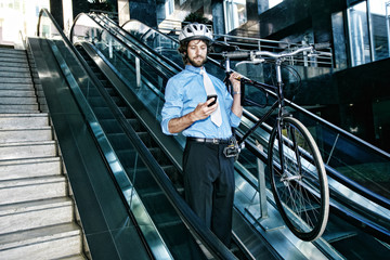 Caucasian businessman carrying bicycle on escalator