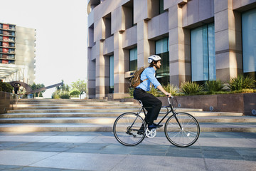 Caucasian businessman riding bicycle outside office building