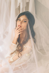 portrait shot of a beautiful girl with perfect skin and elegant hair.Cute young girl sitting in a veil and sad.Beautiful melancholy.Fashionable toning.creative computer colors.