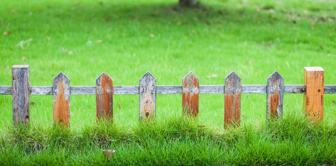 Old small fence on the green lawn in garden