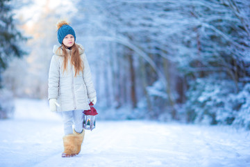 Adorable girl with flashlight and candle in winter on Xmas eve outdoors