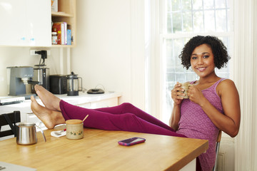 Mixed race woman drinking coffee with feet up in kitchen