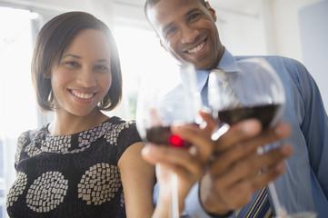 Portrait of happy couple toasting wine glasses