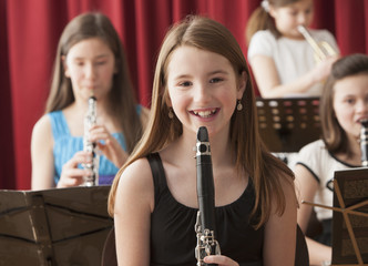 Portrait of smiling Caucasian girl with clarinet on stage
