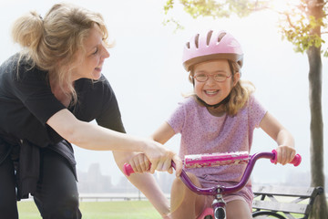 Caucasian mother pushing daughter on bicycle in park