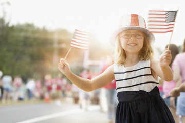 Happy Caucasian girl waving American flags at parade