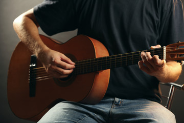 Young musician playing acoustic guitar close up