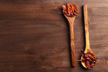 Two wooden spoons with dried chili on the table, close-up