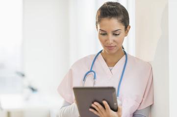 Hispanic nurse using digital tablet in hospital