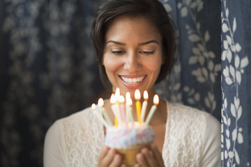 Woman looking down at lit candles on birthday cupcake
