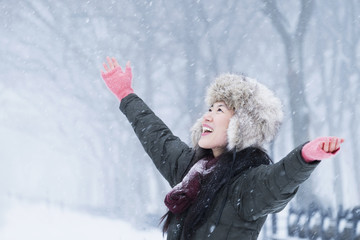 Asian woman cheering in snow