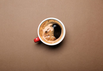 Cup of coffee on brown background, top view