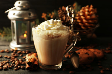 Cup of hot cacao with marshmallow, cookies and lantern on black table