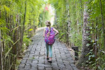 Caucasian girl walking on stone path among bamboo trees